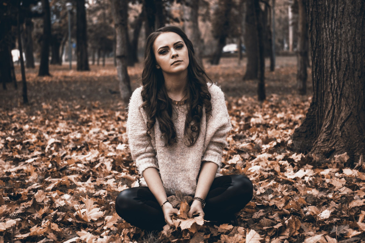 depressed woman sitting in the leaves